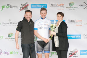 29th of April, 2017; Darragh O'Mahoney, Waterford Racing Club, centre, receives the Stage Winner's jersey from Neil O'Brien, AmberGreen Energy, left, and Paula Nugent, Tour of Ulster, right, on the awards podium on Stage 1 of the AmberGreen Energy Tour of Ulster. Moy, Co. Tyrone. Picture credit: Stephen McMahon / Tour of Ulster