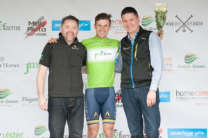 29th of April, 2017; Matteo Cigala, Aqua Blue Sports Academy, centre, recieves the green jersey of Points Leader from Neil O'Brien, AmberGreen Energy, left, and Garry Nugent, Race Director, right, on the awards podium at the finish of Stage 1 of the AmberGreen Energy Tour of Ulster. Moy, Co. Tyrone. Picture credit: Stephen McMahon / Tour of Ulster